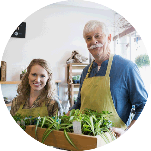 Older gardening business owner posing with young worker