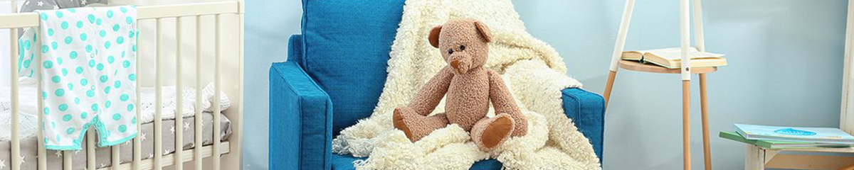 A child's teddy bear sitting on a couch